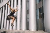 nízký úhel pohled krásná mladá baletka skákání a tančí na ulici