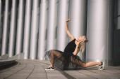 atraktivní mladá baletka v černé sukni tančí na ulici