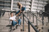 Photo stylish sporty young couple with backpacks sitting on stairs and railings