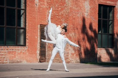 couple of young ballet dancers dancing on city street
