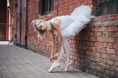 beautiful young ballerina leaning at brick wall and tying pointe shoe