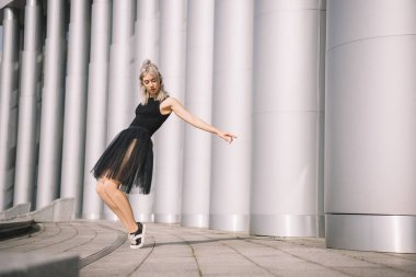 beautiful young woman in black skirt dancing near columns