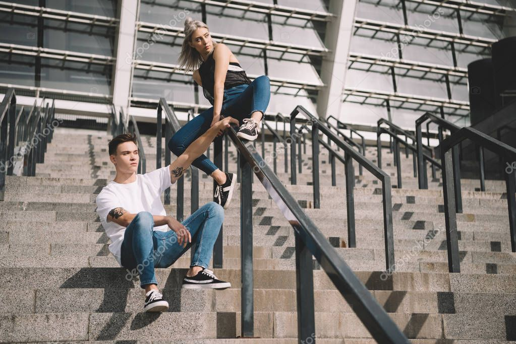 stylish sporty young couple with backpacks sitting on stairs and railings
