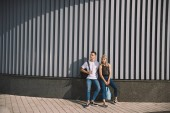 Photo beautiful young couple with backpacks standing together on street