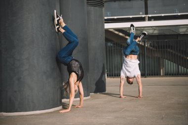 young couple of dancers performing handstand on street
