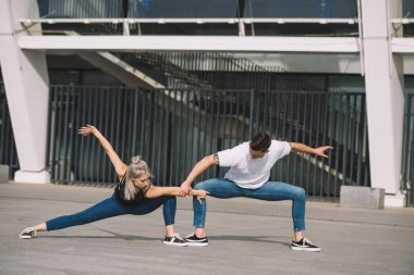 young contemporary dancers performing street dance in city