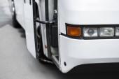 Fotografie zblízka pohled na bílé cestovní autobus světlomety na ulici