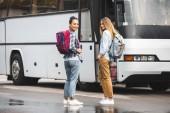 Fotografie multietnické mladé ženy s batohy lodě poblíž cestovní autobus v městské ulici