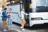 Fotografie Selektivní fokus mnohonárodnostní turisté s batohy do cestovní autobus na ulici