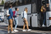 young smiling tourists with rucksacks walking into travel bus at city street