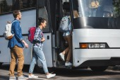 Photo cheerful multiethnic friends with backpacks walking into travel bus at urban street