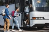 fröhliche multiethnischen Freunde mit Rucksäcken zu Fuß in Reisen Bus bei urban street