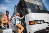 Selektivní fokus Smíšené rasy člověka stojícího s kolový tašku, zatímco jeho přítelkyně do cestovní autobus na ulici