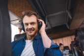 portrait of man in headphones listening music and looking at camera during trip on travel bus