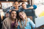 Junger Mann mit gemischter Rasse macht Friedenszeichen mit Freunden, die während der Fahrt im Reisebus ein Selfie auf dem Smartphone machen