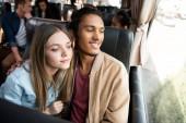 šťastný pár interracial během cesty v autobuse cestovní při pohledu na okna