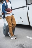 cropped image of man with backpack and rugby ball carrying bag on wheels near travel bus at street