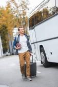 Fotografie pohledný muž s batohem a rugby míč taška na kolečkách poblíž cestovní autobus na ulici