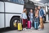 Fotografie multikulturní přátelé s pojezdy tašky představují poblíž cestovní autobus na ulici