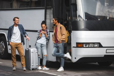 selective focus of multiethnic friends standing with wheeled bag near travel bus at street