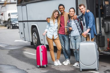 young happy multicultural friends with wheeled bags posing near travel bus at street