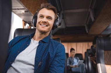 cheerful man in headphones listening music during trip on travel bus