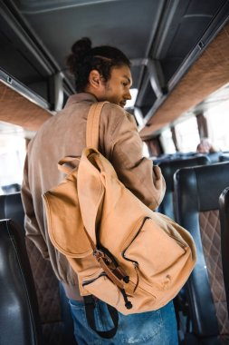 rear view of mixed race male tourist with backpack in travel bus