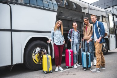 multicultural friends with travels bags posing near travel bus at street