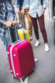 Fotografie oříznutý obraz turistů s stojící poblíž cestovní autobus v městské ulici tašky na kolečkách
