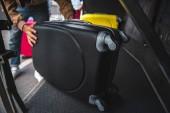 Fotografie Mann steckt Rolltasche in Reisebus an der Stadtstraße