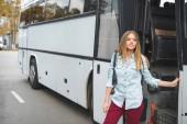 junge Frau mit Rucksack Stand in der Nähe Reisebus bei street