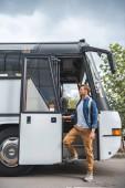 dospělý muž s batoh odstupující od cestovní autobus na ulici