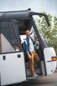 gut aussehend männlichen Reisenden mit Rucksack zu Fuß aus vom Reisebus bei street