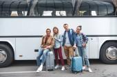multikulturelle Jugendliche mit Rädern Taschen posiert in der Nähe von Reisen Bus an Stadtstraße