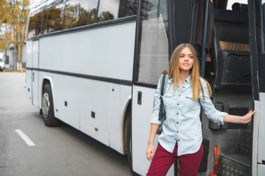 young woman with rucksack standing near travel bus at street