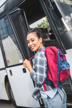 selective focus of asian female tourist with backpack looking at camera near travel bus at city street