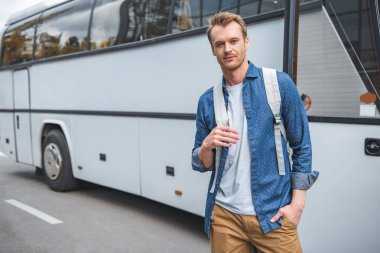 adult man with backpack posing near travel bus at street