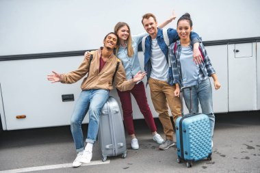 multiethnic happy friends with travels bags gesturing near bus at street