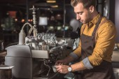 handsome young barista preparing coffee with coffee machine in cafe