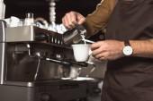 Fotografie zugeschnittenen Schuss Barista gießt Milch in Kaffee während der Vorbereitung es im café