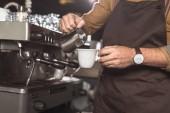oříznutý snímek barista v zástěře nalévání mléka do kávy při přípravě v restauraci
