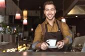 Lächelnder junger Barista mit Tasse Kaffee und Blick in die Kamera