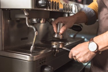 cropped shot of barista pressing coffee into holder for coffee machine