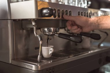 cropped shot of barista preparing coffee with coffee machine in cafe