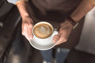 cropped shot of barista holding cup of fresh made cappuccino