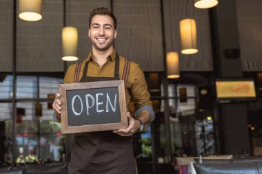 attractive smiling waiter holding chalkboard with open inscription in cafe