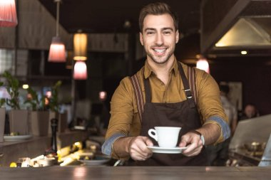 Smiling young barista holding cup of coffee and looking at camera stock vector