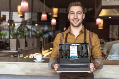 handsome young waiter holding laptop with linkedin website on screen in cafe