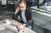 jistý mladý nezávislý pracující s přenosným počítačem a mluví po telefonu v kavárně
