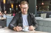 Fotografie usmíval se mladý muž s šálkem kávy pomocí smartphone v kavárně
